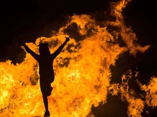 A New Mexico State University cheerleader is pictured in front of the NMSU bonfire on Friday.