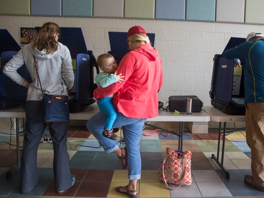 Abigail Turner holds on to her daughter, Amelia, 1, as she casts her vote for this years election at Plaza Park School in Evansville on Tuesday morning.