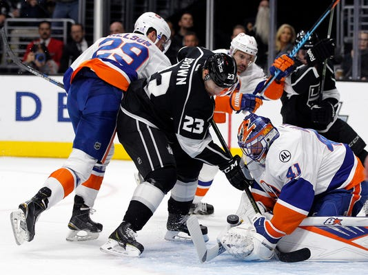 New York Islanders goalie Jaroslav Halak (41), of Slovakia, stops a shot as Los Angeles Kings right wing Dustin Brown (23) looks for a rebound next to Islanders center Brock Nelson (29) during the second period of an NHL hockey game in Los Angeles, Thursday, Nov. 12, 2015. (AP Photo/Alex Gallardo)