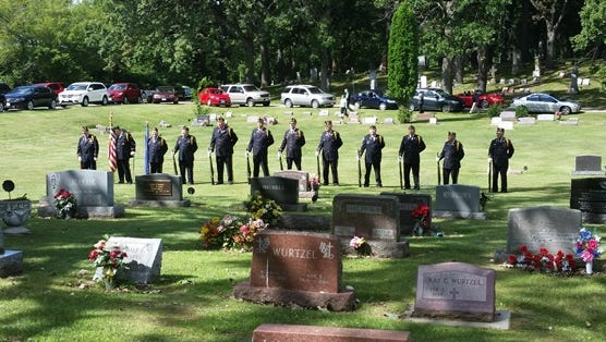 Fond du Lac Trier-Puddy American Legion Post No. 75 Honor Guard members stand in front of a grave at the funeral of a veteran.