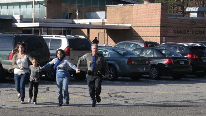 In this Dec. 14, 2012 photo provided by the Newtown Bee, a police officer leads two women and a child from Sandy Hook Elementary School in Newtown, Conn., where a gunman opened fire, killing 26 people, including 20 children.