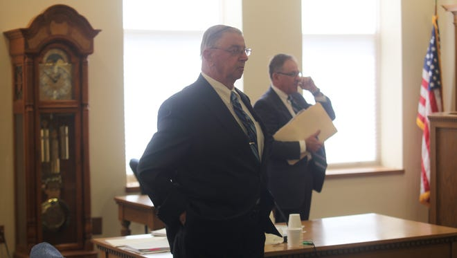 Henry Rayhons, foreground, stands during a break in his Hancock District Court trial Wednesday.