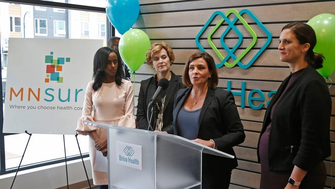 In this Oct. 26, 2017, photo, Allison O'Toole, second from right, speaks to the media at the new offices of Briva Health, MNsure's largest enrollment partner, in Minneapolis. Health care consumers in most of the country are encountering a world of confusion and chaos as the open enrollment period to sign up for coverage approaches. The outlook is decidedly different in the 12 states that operate their own marketplaces. California, Colorado, Minnesota and other states that operate autonomous exchanges are pulling out all the stops to inform consumers. Also shown, from left, Hodan Guled, chief executive officer of Briva Health, Minneapolis Major Betsy Hodges and at right, Emily Piper, commissioner of Minnesota Human Services.