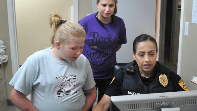 Hilary Wheeler, center, and her daughter, Zailey Barnes, left, watch as Lieutenant Lahoma Vaughn, Burkburnett Police Department, looks through the Take Me Home database system. The Take Me Home database was developed by the Pensacola, Fl, police department for people that might need special assistance when they are alone during an emergency.