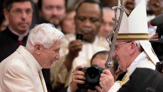 Pope Francis, right, salutes Pope Emeritus Benedict XVI, left, at the end of a consistory inside the St. Peter's Basilica at the Vatican on Feb. 22, 2014.