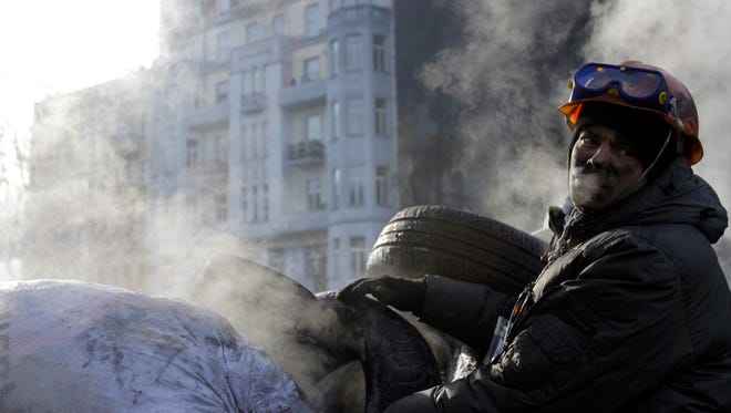 A protester guards the barricade in front of riot police in Kiev, Ukraine, on Jan. 27, 2014.