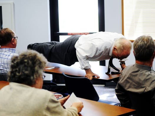 Mike Myers, independent candidate for Governor of South Dakota, does push ups on a table after being told he had enough signatures to make the ballot by his campaign manager, Tara Volesky, during a joint news conference with Republican candidate, Lora Hubbel, on Wednesday, April 23, 2014, at the Caille Branch of the Siouxland Libraries in Sioux Falls. (Joe Ahlquist / Argus Leader)
