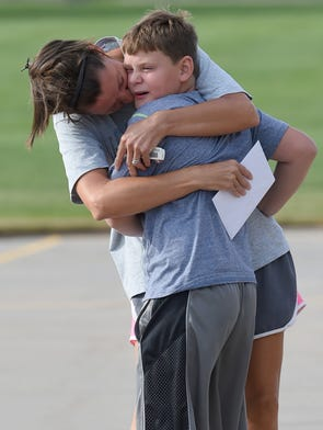 Christie Carson, hugs and kisses her son, Henry, 9, a fourth grader at Kruse Elementary School before the first day of school at Kruse Elementary School Tuesday Aug. 19, 2014.