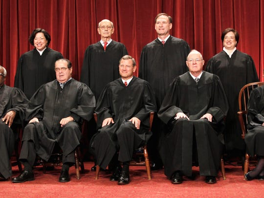 Supreme Court justices, seated from left, Clarence Thomas, and Antonin Scalia, Chief Justice John Roberts, Anthony M. Kennedy, and Ruth Bader Ginsburg. Standing, from left are Sonia Sotomayor, Stephen Breyer, Samuel Alito Jr., and Elena Kagan.