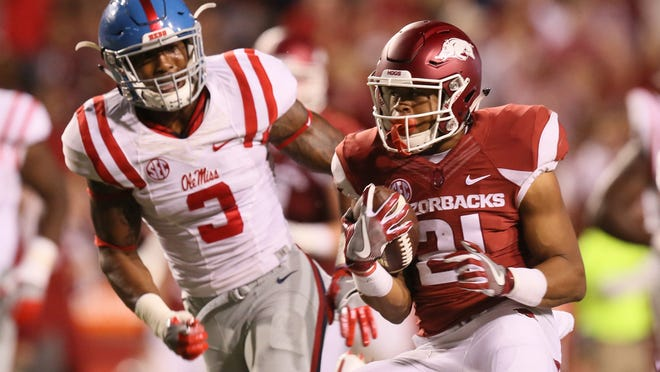 Oct 15, 2016; Fayetteville, AR, USA;  Arkansas Razorbacks running back Devwah Whaley (21) rushes as Ole Miss Rebels linebacker DeMarquis Gates (3) defends in the second quarter at Donald W. Reynolds Razorback Stadium. Mandatory Credit: Nelson Chenault-USA TODAY Sports