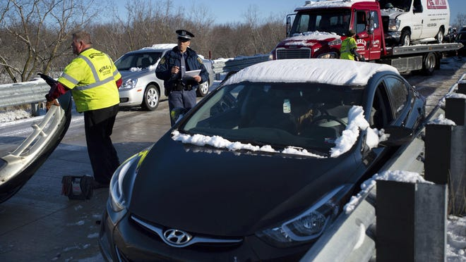 Emergency personnel clear the scene of a pile up on the I-196 westbound off ramp to M-11 (28th Street) in Grandville, Mich., on Monday, April 15, 2019. Authorities say at least two people were injured in a pileup involving a school bus and several other vehicles along an icy interstate off-ramp in western Michigan.