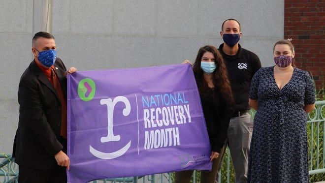 Somersworth Mayor Dana Hilliard and SOS Recovery raise the purple flag.