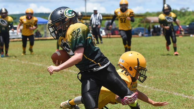 The Packers' Elijah Rogers (22) is tripped up by Eagles player Eric Tedtaotao (16) during their Guam National Youth Football Federation game at Eagles Field on Sept. 3.