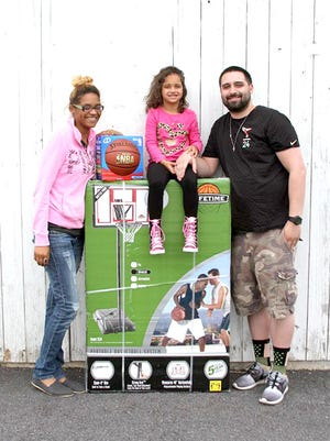 Ryvre Dunalp-Wheat, 5, and her parents, Jasmine Wheat and Travis Dunlap, pose with a basketball hoop and basketball that Ryvre won at the Lebanon Federal Credit Union celebration of National Credit Union Youth Month in April. Any youth member ages 12 and under who opened a new account was eligible to win. They also received a free T-shirt with another prize if they referred a friend. Youth members also received mini squeeze dumbbells and a protein snack mix.