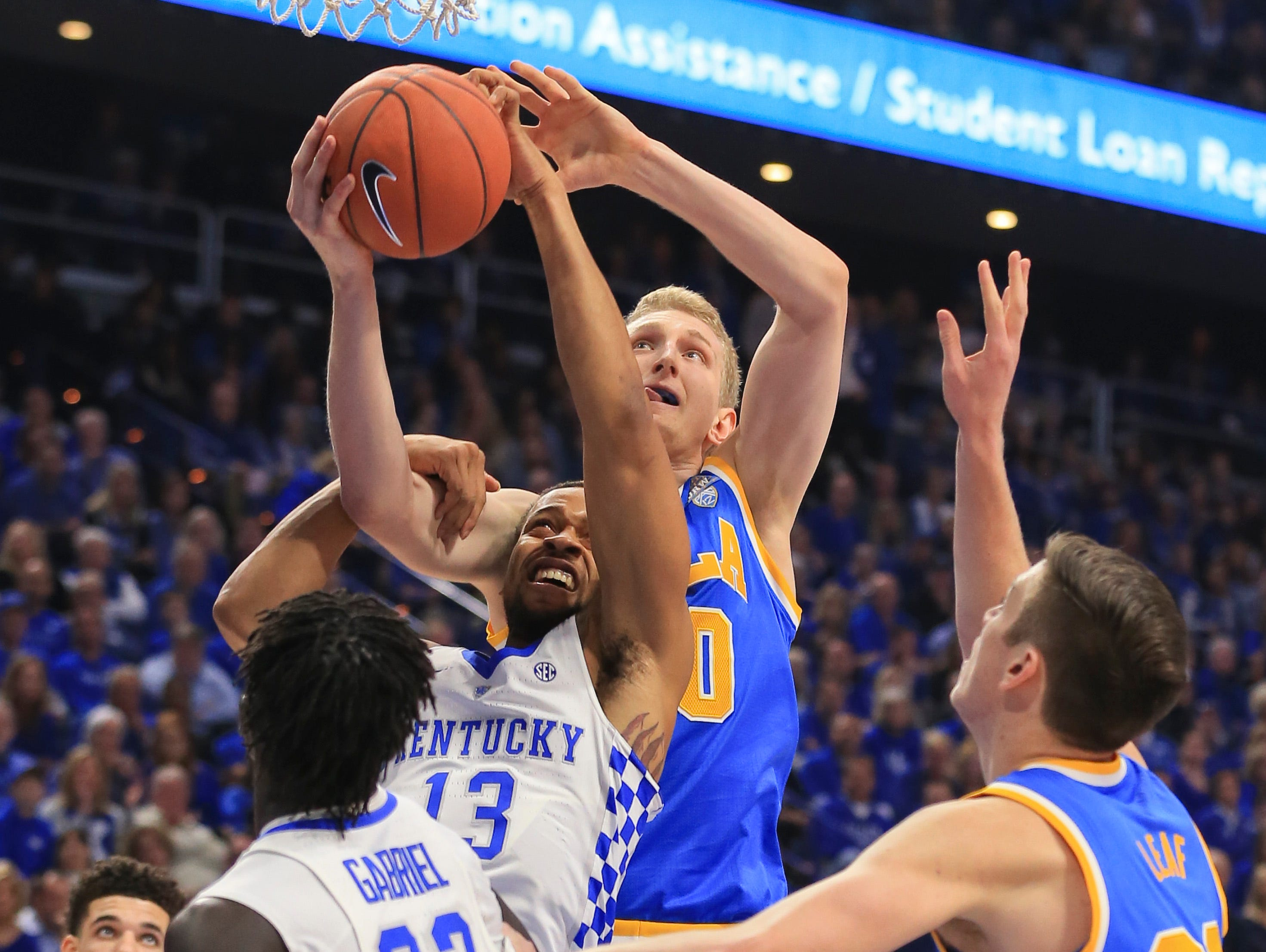 Kentucky's Isaiah Briscoe had to use his hand to get around a pressuring Thomas Welsh of UCLA in the first half in the Bruins' upset win over the Wildcats 97-92 Saturday afternoon at Rupp Arena.