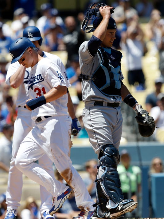 Los Angeles Dodgers' Joc Pederson, left, scores from third base on a throwing error by Tampa Bay Rays catcher Luke Maile, right, during the second inning of a baseball game in Los Angeles, Wednesday, July 27, 2016. (AP Photo/Alex Gallardo)