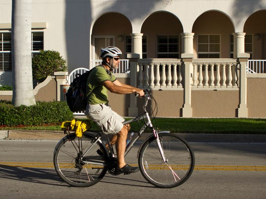 Andy Getsch rides his bike on West First Street on his way to work in downtown Fort Myers on Thursday morning.