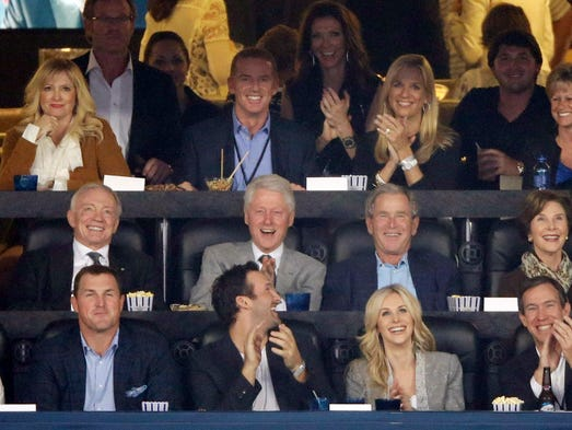 From center left, Dallas Cowboys owner Jerry Jones, former presidents Bill Clinton and George W. Bush and former first lady Laura Bush as well as Cowboys head coach Jason Garrett, second from top left, watch action between Connecticut and Kentucky.