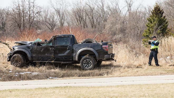 A Fond du Lac police officer takes a photo of a pick-up truck Monday, after it was pulled out of an area of trees on State 23 near Fond du Lac County K where it crashed on the east side of Fond du Lac. The lone occupant of the truck was flown by Flight For Life to a local trauma center.