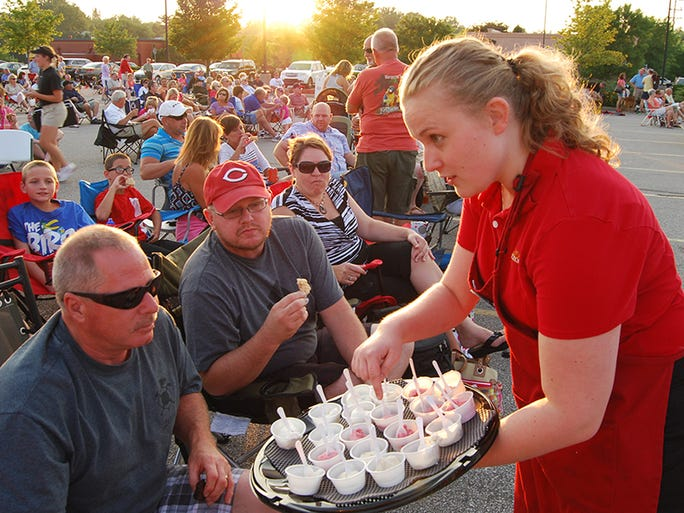 Jenna Sharp of Cold Spring and Cold Stone Creamery handed out samples to from left, Tim Jaeger of Cincinnati and Dave Hall of Independence during the city of Crestview Hills summer concert held Friday, July 11, at Crestview Hills Town Center.