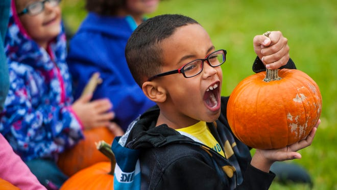 Jacob Spoiling, 6 1/2, pretends to take a bite out of his pumpkin during the Togerson's Farm pumpkin giveaway at Morningside Elementary School Tuesday. Togerson's gave a free pumpkin to every first-grade student in Cascade County, totaling 1,700 squash.