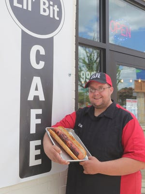 Lil' Bit Cafe chef Micah Townsend shows off the Akron eatery's pounder hot dog Friday.