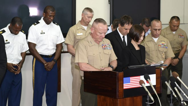 Lt. Gen. Lawrence D. Nicholson, front left, commanding general, III Marine Expeditionary Force, offers silent prayers for a woman who was killed on the southern Japanese island, at the USMC Camp Foster in Okinawa, Japan. The U.S. military in Japan is restricting celebrations and off-base alcohol consumption in Okinawa after a former Marine was arrested on suspicion of killing a woman on the island.
