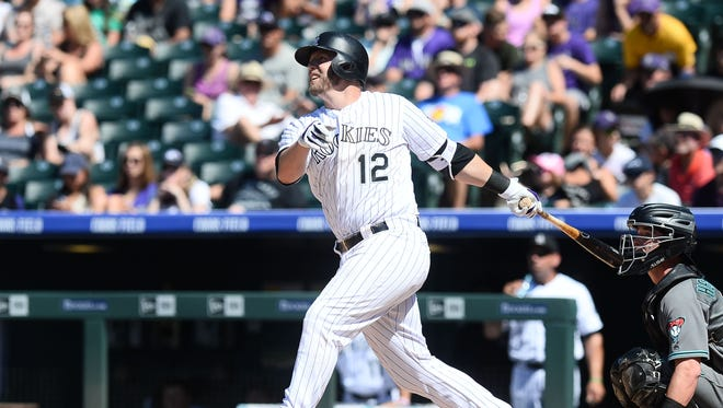 Jun 26, 2016: Colorado Rockies first baseman Mark Reynolds (12) hits a sacrifice fly ball to drive in shortstop Trevor Story (not pictured) in the fourth inning against the Arizona Diamondbacks at Coors Field.