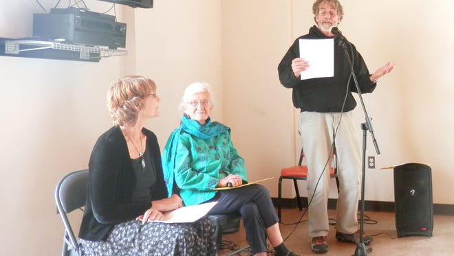 Stewart Warren, at right, reads poetry during Sunday's Seed Celebration at the Volunteer Center of Grant County.