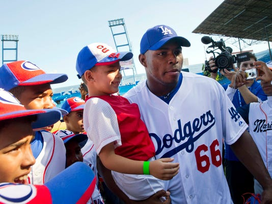 "Los Angeles Dodgers player Yasiel Puig, from Cuba, holds a young baseball player as he poses for photos before giving a baseball clinic to children in Havana, Cuba, Wednesday, Dec. 16, 2015. ""We're going to give our best on this visit and we appreciate the opportunity we've been given,"" said Puig, who left Cuba on a smuggler's fast-boat in 2012. ""Everything else we leave to God and destiny."" (AP Photo/Ramon Espinosa)"
