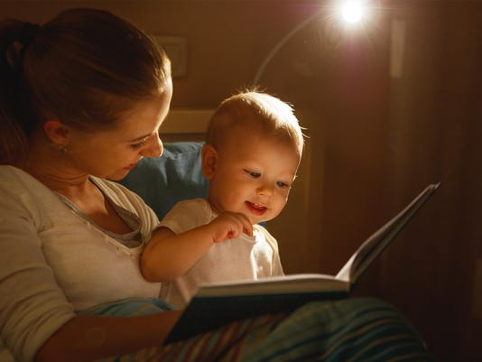 mother reads to baby book in bed