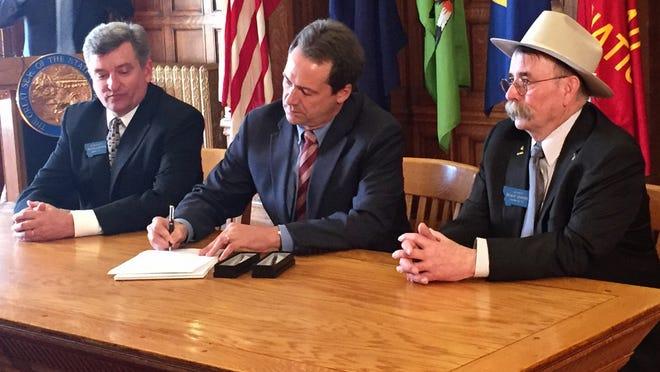 Rep. Frank Garner, R-Kalispell, and Sen. Duane Ankney, R-Colstrip, flank Gov. Steve Bullock as he signs a bill banning dark money contributions to Montana elections.