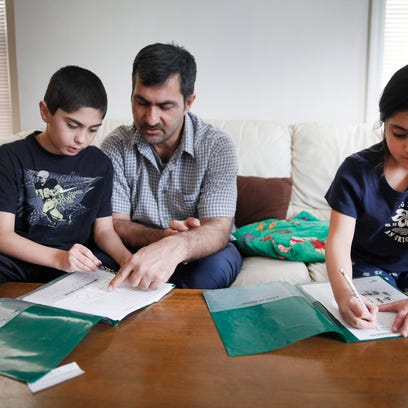 Aziz Sharifi, center, helps his children Khaybar Sharifi,