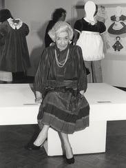 Florence Eiseman sits near some of her clothing designs