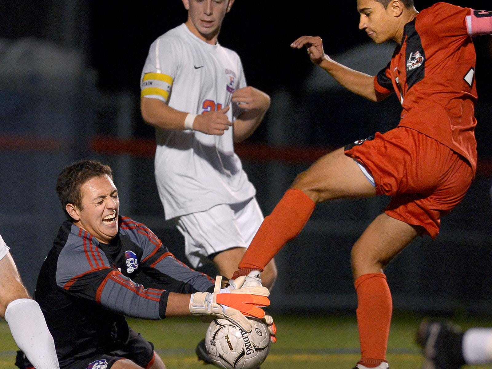 Fairport goalie John Flannery smothers the ball off the foot of HiltonÕs Matthew DeFeo during a regular season game at Fairport High School on Wednesday, Oct. 5, 2016. Fairport and Hilton played to a 3-3 draw.