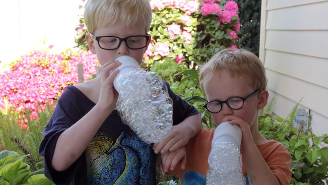 """Evander and Gideon Mann compete for making the biggest bubble bunching using """"wands"""" they created out of water bottles and socks."""