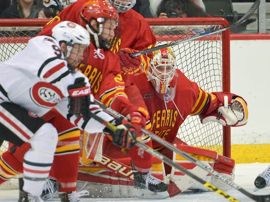 St. Cloud State's Joey Benik (9) reaches for the puck