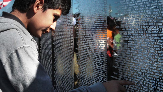 Omar Moctezuma carefully reads the names on the Vietnam Traveling Memorial Wall at the Chennault Aviation and Military Museum.