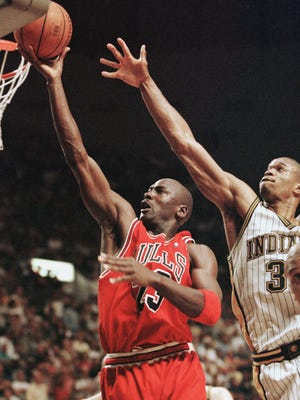 INDIANAPOLIS, IN - MAY 29:  Michael Jordan (L) of the Chicago Bulls drives to the basket past Antonio Davis (R) of the Indiana Pacers 29 May during the second half of game six of their NBA Eastern Conference finals game at Market Square Arena in Indianapolis, IN. The Pacers won the game 92-89 to tie the series at three games apiece forcing a game seven on 31 May.