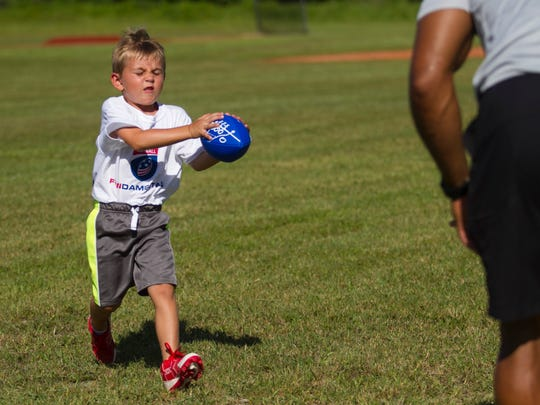 Owen Underhill makes a catch while doing defensive back drills with Nate Allen at a free youth football camp at McGregor Baptist Church on Saturday.