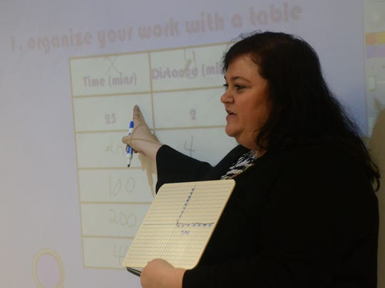 Kathy Touchet, an eighth-grade math teacher at Northwood High School, explains how students are taught to use a graph to work out math problems during Math Night on Dec. 17.