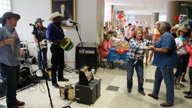 """Guests dance to the music of Leroy Thomas and the Zydeco Roadrunners as Cancer Center of Acadiana at Lafayette General hosts a Cancer Survivor's Day party and program including live music, guest speakers, door prizes and presentations Friday, June 5, 2015, at the Burdin-Riehl Center in Lafayette. The theme for the event was """"Give Cancer the Boot"""" and guest were encouraged to wear cowboy-themed attire."""