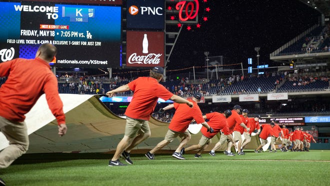 Members of the ground crew hurry to cover the infield during a rain delay in the sixth inning of an interleague baseball game between the New York Yankees and Washington Nationals at Nationals Park, Tuesday, May 15, 2018, in Washington.