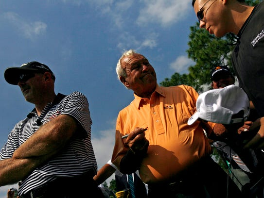 Arnold Palmer, center, signs an autograph for a fan