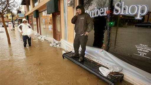 Erik Wagner, left, owner of Erik's Barber Shop in Healdsburg Calif, and his employee James Uribe, right, check the flooding, in the area, Thursday in Sonoma County. A powerful storm churned down the West Coast Thursday, bringing strong gales and much-needed rain and snow that caused widespread blackouts in Northern California and whiteouts in the Sierra Nevada. Sonoma County authorities recommended hundreds of people to evacuate the lowest lying areas near the Russian River, which is projected to start overflowing overnight.