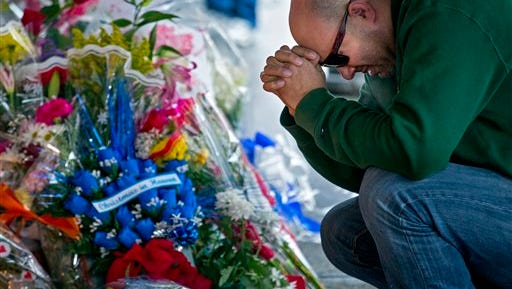 Department of Homeless Services NYPD Sgt. Frank Lopez bows his head at a makeshift memorial Tuesday near the site where New York Police Department officers Rafael Ramos and Wenjian Liu were murdered in Brooklyn.
