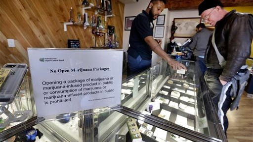 In this Tuesday, Dec. 30, 2014, photo, Cannabis City clerk Will Bibbs, left, helps a customer looking over a display case of marijuana products at the shop in Seattle. A year into the nation's experiment with legal, taxed marijuana sales, Washington and Colorado find themselves with a cautionary tale for Oregon, Alaska or other states that might follow suit: They're wrestling not with the federal interference many initially feared, but with competition from their own medical marijuana systems or even outright black market sales. (AP Photo/Elaine Thompson)