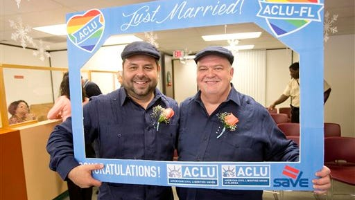Edgard Perez, left, 40, and his spouse Charles Windham, right, 53, pose for a photo after they were married at the marriage license bureau, Tuesday, Jan. 6, 2015 in Miami. Miami-Dade Circuit Judge Sarah Zabel presided over Florida's first legally recognized same-sex marriages Monday afternoon. Still, most counties held off on official ceremonies until early Tuesday, when U.S. District Judge Robert L. Hinkle's ruling that Florida's same-sex marriage ban is unconstitutional took effect in all 67 counties. (AP Photo/Wilfredo Lee)