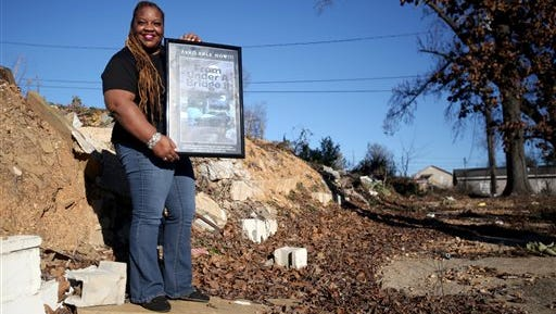 Blossom Rogers stands with a poster promoting her book on land in Alberta that will be the future location to a transitional home for recovering women, on Sunday in Tuscaloosa, Ala. Rogers, a former drug addict herself, has been clean for 10 years and hopes to be cutting the ribbon on the home in a year.