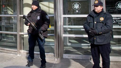 A Homeland Security police officer, left, joins a Federal Court policeman, right, as security is enhanced during the arraignment of two men on terrorism related charges today in Brooklyn, N.Y. The men were arrested along with a third man today on charges of plotting to travel to Syria to join the Islamic State group and wage war against the U.S.